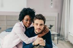 Mellan skilda raser unga par som kopplar av och har gyckel på säng afrikansk kvinna arkivfoton