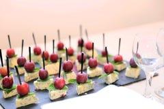 Mellanmål av ädelost med mintkaramellen och oliv på steknålar på en blurr Arkivfoton