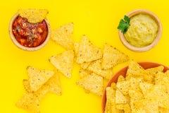 Mellanmål för parti Mexicanska nachos nära salsa- och guacamolesause på bästa sikt för gul bakgrund royaltyfria foton