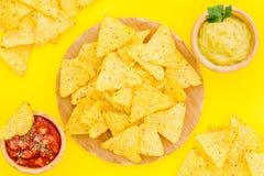 Mellanmål för parti Mexicanska nachos nära salsa- och guacamolesause på bästa sikt för gul bakgrund arkivfoto