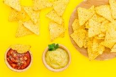 Mellanmål för parti Mexicanska nachos nära salsa- och guacamolesause på bästa sikt för gul bakgrund arkivfoton