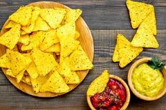 Mellanmål för parti Mexicanska nachos nära salsa- och guacamolesause på bästa sikt för mörk träbakgrund arkivbilder