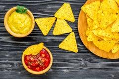 Mellanmål för parti Mexicanska nachos nära salsa- och guacamolesause på bästa sikt för svart bakgrund arkivbild