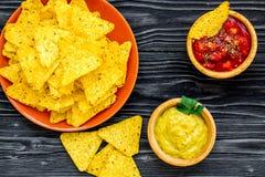 Mellanmål för parti Mexicanska nachos nära salsa- och guacamolesause på bästa sikt för svart bakgrund arkivfoto