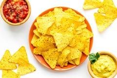 Mellanmål för parti Mexicanska nachos nära salsa- och guacamolesause på bästa sikt för vit bakgrund arkivfoton
