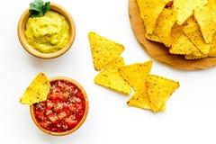 Mellanmål för parti Mexicanska nachos nära salsa- och guacamolesause på bästa sikt för vit bakgrund arkivbilder