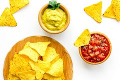 Mellanmål för parti Mexicanska nachos nära salsa- och guacamolesause på bästa sikt för vit bakgrund arkivfoto