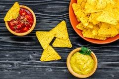 Mellanmål för parti Mexicanska nachos nära salsa- och guacamolesause på svart utrymme för kopia för bästa sikt för bakgrund fotografering för bildbyråer