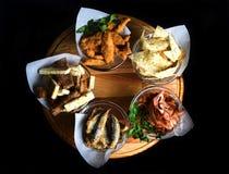 Mellanmål till öl i glasföremål på ett träbräde Chiper mellanmål, skorpor, torkade kött, stekt fisk Fotografering för Bildbyråer