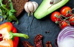 Mellanmålingredienser: bröd avokado, arugula, tomater, vitlök Arkivbilder