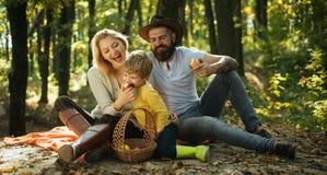 mellanm?ltid Lycklig familj med ungepojken som kopplar av, medan fotvandra i frukter för mellanmål för mat för skogkorgpicknick s arkivfoton