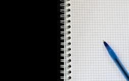 Mellanrum kvadrerad pappers- anteckningsbokspiral med blåttpennan på bästa sikt för svart bakgrund Royaltyfri Foto