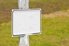 Mellanrum som annonserar affischtavlan för vit metall i ett fält av torkat gräs - bild med kopieringsutrymme arkivfoto