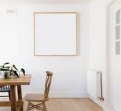 Mellanrumet inramade trycket på den vita väggen i dansk utformade inre dinin Fotografering för Bildbyråer