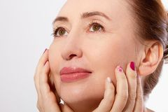 Mellersta ålderkvinna för makro som trycker på hennes framsida och gör ren hud Collagen- och framsidainjektioner Anti--åldras och royaltyfria bilder