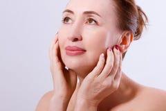Mellersta ålderkvinna för makro som trycker på hennes framsida och gör ren isolerad hud Collagen- och framsidainjektioner Anti--å arkivfoton