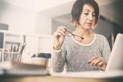 Mellersta ålderkvinna som använder datoren royaltyfri bild