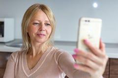 Mellersta ålderkvinna som hemma tar en selfie royaltyfri fotografi