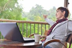 Mellersta ålderkvinna som kopplar av med bärbar datordatoren fotografering för bildbyråer