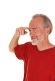 Mellersta ålderman som pekar på pannan Arkivfoton