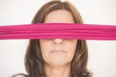 Mellersta åldrig kvinna för stående med ögonbindeln Arkivbilder