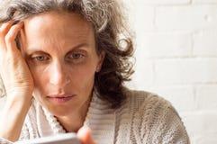 Mellersta åldrig kvinna som använder telefonen Arkivfoto