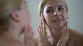 Mellersta åldrig kvinna som tillfredsställs med framsidavillkor efter skönhetterapeutbesök stock video
