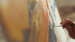 Mellersta åldriga målarfärger för kvinnakonstnärolja på kanfas som rymmer träpaletten på varvar stock video