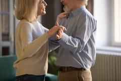 Mellersta åldriga par och att älska frun och maken som hemma dansar arkivfoto