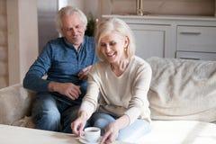 Mellersta åldriga par som sitter på soffan som vilar dricka te arkivbilder