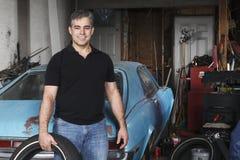 Mellersta åldrigt maninnehavgummihjul utanför hans garage Royaltyfria Bilder