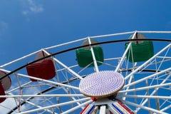 Mellersta och övredel av ferrishjulet med röda och gröna bunkar mot blå himmel med tunna moln Fotografering för Bildbyråer