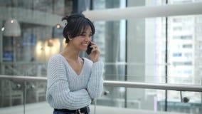 Mellersta skjuten ultrarapid av asiatiskt kvinnligt skratta samtal p? telefonen, medan g? lager videofilmer