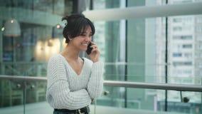 Mellersta skjuten ultrarapid av asiatiskt kvinnligt skratta samtal p? telefonen, medan g? stock video