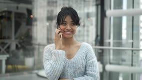 Mellersta skjuten ultrarapid av det asiatiska kvinnliga anseendet som skrattar samtal på telefonen stock video