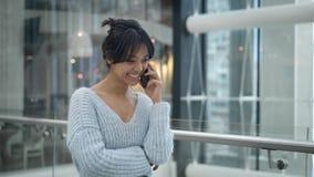 Mellersta skott av asiatiskt kvinnligt skratta samtal på telefonen, medan gå arkivfilmer