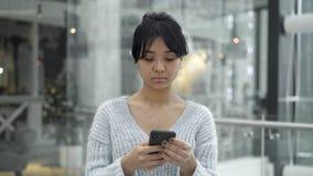 Mellersta skott av den asiatiska kvinnlign som går med en telefon på fönsterbakgrund