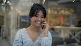 Mellersta skott av det asiatiska kvinnliga anseendet som skrattar samtal på telefonen