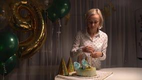 Mellersta skott av kvinnabelysningstearinljus på den smakliga födelsedagkakan förbereda sig för deltagare arkivfilmer