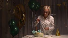 Mellersta skott av kvinnabelysningstearinljus på den smakliga födelsedagkakan förbereda sig för deltagare lager videofilmer