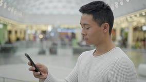 Mellersta skott för profil av den asiatiska manliga bläddra telefonen på stor galleriabakgrund arkivfilmer