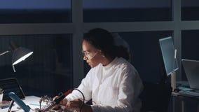 Mellersta slut upp av afrikansk amerikanteknikern som gör prov på moderkortet i labb Forskare som arbetar i ett laboratorium med arkivfilmer