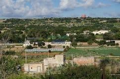 Mellieha, Malta - 30 dicembre 2018 - pannelli solari sulla casa in mezzo ai campi di agricoltura sotto la torre rossa immagine stock libera da diritti