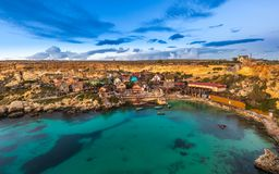 Mellieha, Malta - The famous Popeye Village at Anchor Bay at sunset. With amazing colorful clouds and sky Stock Photos