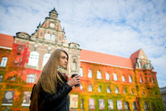 Mellow autumn. The lovely girl student has coffee. She stands near the building which is completely twined wild grapes. Motley leaves give to the building Stock Photos
