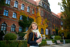 Mellow autumn. The lovely girl student has coffee. She stands near the building which is completely twined wild grapes. Motley leaves give to the building Royalty Free Stock Images