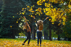 Mellow autumn. Two cheerful girls of student walk in the park. Mellow autumn. Two cheerful girls are students walk in the autumn park. The lawn in the park is Royalty Free Stock Images