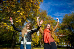 Mellow autumn. Two girls are students cheerfully spend time in the city park. Royalty Free Stock Image
