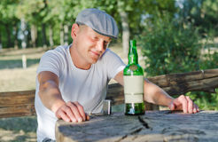 Mellow drunk smiling at his bottle of alcohol. Mellow drunk sitting at an outdoor rustic wooden table in a park smiling at his bottle of alcohol Royalty Free Stock Images
