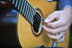 Mellow guitar. Man's hand plucking the nylon strings of a guitar Stock Image